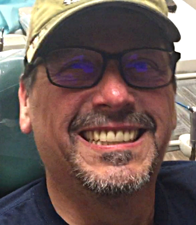 Patient smiling after tooth replacement with traditional dentures